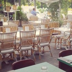 #SikaDesign Monique chair shown in a French style bistro cafe complete with rattan dining chairs and white cast iron bistro table bases. Available at http://www.sika-design.us/products/monique-outdoor-rattan-side-chair