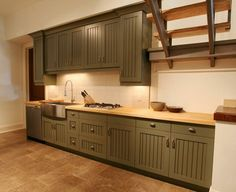 This basement kitchenette features a butcher block counter top and apron sink.