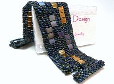 A modern geometric cuff bracelet woven of deep blue Delica seed beads and Tila beads in gold, silvery gray and iris-finished blue tones.  Im a little hesitant to say so, but I remember the 60s. I was but a child - but I remember the Mod clothing styles, go-go boots, and those great little a-line dresses with Mondrian-inspired color blocks. And although I cant say I have any nostalgia for the boots, those color blocks still resonate with me - hence my Modern Blocks Collection!  This member of…