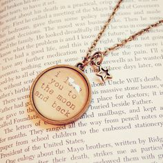 This whimsical antique bronze necklace features a handmade round pendant bearing the words i love you to the moon and back. The quote has