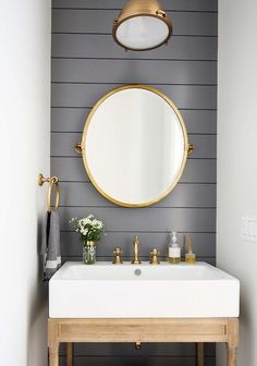 Dark Gray Shiplap Trim with Oval Brass Pivot Mirror - Cottage - Bathroom Small, stylish powder room boasts an oval brass pivot mirror mounted to a dark gray shiplap backsplash and matched with a brass industrial pendant. Powder Room Storage, Powder Room Paint, Blue Powder Rooms, Powder Room Wallpaper, Modern Powder Rooms, Powder Room Decor, Powder Room Design, Powder Room Mirrors, Small Powder Rooms