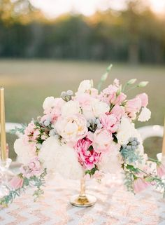 Romance reigns with this pastel pink peony centerpiece. While this is technically a bridal bouquet, it's got that balance of formal and casual that would work perfectly in a simple glass vase on a tablecloth covered picnic table.