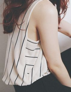 Slim stripes of black in different directions on a sleeveless shirt