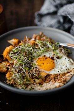 Filling Grain bowls with farro, hummus, smoky roasted cauliflower, fried eggs, and microgreens.