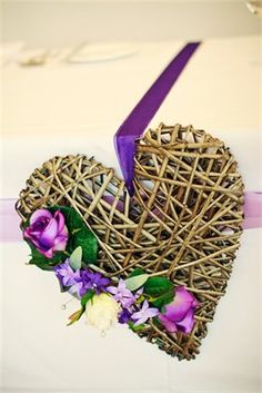 Beautiful wicker heart decorated with artificial flowers