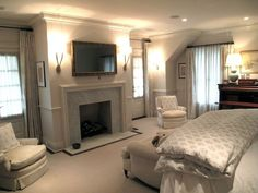 Figless Manor - Elegant bedroom design with flatscreen TV over marble fireplace, two-tone greige walls paint color with chair rail, traditional chairs with paisley pillows, ivory linen sofa with caster legs and paisley bedding.