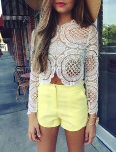 Comprar ropa de este look: https://lookastic.es/moda-mujer/looks/blusa-de-manga-larga-de-encaje-blanca-pantalones-cortos-amarillos-pulsera-dorada/12286   — Blusa de Manga Larga de Encaje Blanca  — Pantalones Cortos Amarillos  — Pulsera Dorada