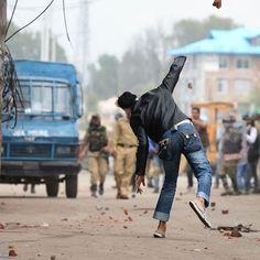 Un uomo lancia un sasso alla polizia, durante scontri tra polizia indiana e manifestanti kashmiri dopo che il coprifuoco - in vigore da 52 giorni - era stato tolto in alcune zone del Kashmir