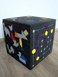 Genial essa caixa de guardar brinquedos. Ela é forrada com carpete e cada face é decorada como um jogo de tabuleiro. As pecinhas são de feltro com velcro, para fixar no carpete. (via Dam! Design)