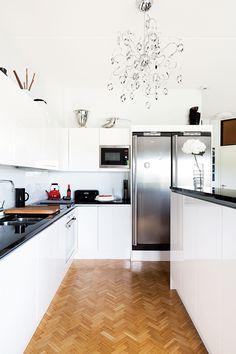 Keittiö on Saari-keittiön mallistosta. Kiiltävän valkoiset kaapistot näyttävät hyvältä asunnon alkuperäisen kalanruotoparketin kanssa. Korkea saareke rajaa keittiön olohuoneesta.