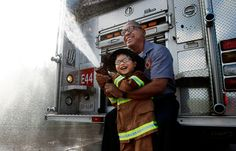 With a big smile and official gear, 6-year-old Johan Pinson becomes a honorary fireman for a day while spraying a hose with help from Memphi...