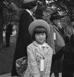 A girl awaiting the evacuation bus with her family. Hayward, California, 1942.  Dorothea Lange