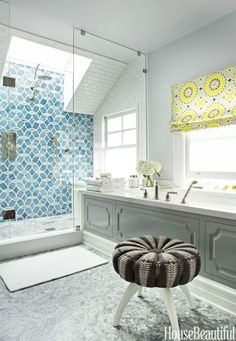 The circular motif of Ann Sacks's Beau Monde Glass Mosaics tile in this San Francisco master bathroom is echoed by a round stool found on Etsy and a Roman shade in Schumacher's Soleil L.A. Print.