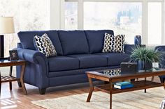 Blue couches, wood tables, neutral walls and flooring.