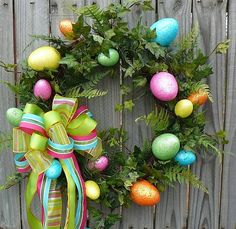 "This adorable wreath features sparkly foam eggs in cute bright colors. The eggs can be found in a lush bed of realistic ivy and fern. A bright bow made with wired ribbon (for easy re fluffing) finishes off the look. This wreath was created using an 18"" grapevine wreath."