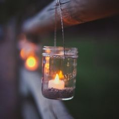 Add warm rustic appeal to your outdoor wedding by hanging candles in mason jars on fence posts after the sun goes down.
