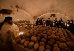 A Romanian Orthodox priest holds religious services for the dead as nuns hold candles inside to the ossuary of Pasarea monastery during Easter celebration in Pasarea village, Bucharest, on May 4, 2013.