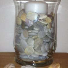 Use rocks and shells from the beach in a vase for decoration.