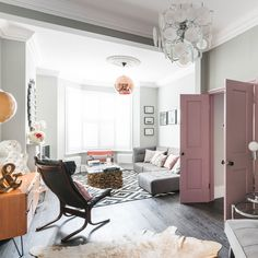 Eclectic modern living room with grey walls and pink doors