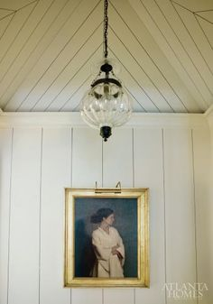 I really like the casual look of the shiplap with the gold-framed traditional painting and the traditional glass chandelier.  Traditional, yet casual, simple.