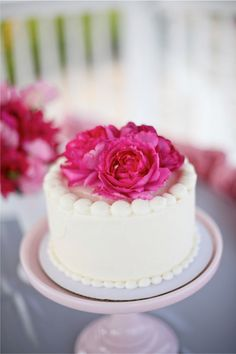 mini wedding cake with hot pink flowers atop.