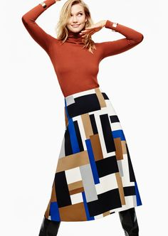 Karlie wears a turtleneck and graphic print midi-skirt