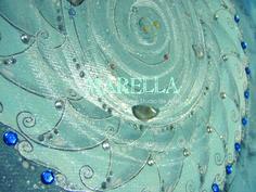Mandala em aquarela azul acinzentado representando o elemento ar. Diâmetro médio de 25cm. Moldura padrão branca com vidro.