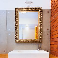 A Bathroom Mirror Which Is Custom Made With Gold Frame