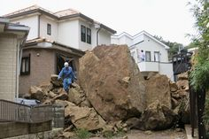 2013.10.16 - A man navigated big rocks that struck a home after Typhoon Wipha caused a landslide in Kamakura, Japan. At least 17 people were killed as the typhoon hit Tokyo and surrounding areas Wednesday, speeding northeast along Japan's coast. (Kyodo/Reuters)