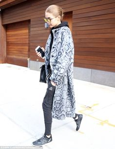 Stunner: She accessorised with large black aviator shades while carrying along a black lea...