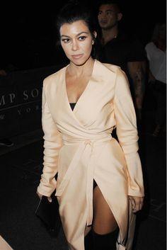 Kourtney Kardashian wears a silk wrap dress with a black bodysuit and thigh-high boots