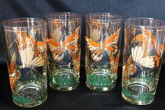 This+set+of+four+tumbler+drinking+glasses+are+made+by+Culver+during+the+1950s.+They+are+part+of+the+Butterfly+Nature+[attern+which+features+large+orange+and+beige+butterflies+circling+around+a+clear+glass.+There+are+blades+of+green+grass+circling+around+the+base+of+the+glass.+They+are+accented+wi...
