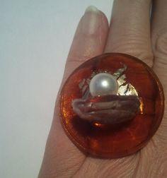 Anello regolabile con base in vetro color topazio, su cui poggia, a sbalzo, elemento in cristallo con perla con inserito perno metallico. Decoro in foglia oro. Pezzo unico e non ripetibile.