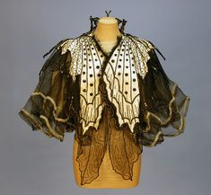 PINGAT JET BEADED BUTTERFLY EVENING CAPE, 1890's. Cream satin with chiffon shoulder drape beneath two layers of stiffened black net decorated as butterfly wings with silver sequins and faceted jet beads, the high neck having a large beaded wire butterfly at back.