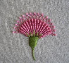 whipped spiderweb    The cool thing about this flower is that each spoke is not just a straight stitch, it is a long and skinny chain stitch. Once the whipping is done, the sides of each chain are pulled together to form the diamonds at the top. This is from Jane Nicholas' book Stumpwork Embroidery.