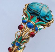 Carved scarab, enamel and gold Egyptian-revival bangle bracelet.  Marcus & Co.   Marcus and Co. was the chief rival of Tiffany & Co during the first part of the 20th century.