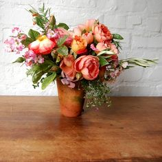 Pretty table arrangements of garden roses and fragrant herbs in terracotta pots   The Natural Wedding Company