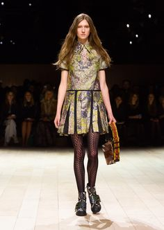 A metallic green pleated shirt dress styled with The Buckle Boot with stud detailing, and The Patchwork in gold sequins and House check. Discover the collection at Burberry.com