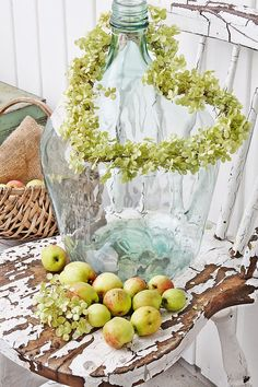 Fall design vignette + apples + burlap + pale green leaf heart wreath + chippy white vintage country chair + wood basket + large blue glass jug + country + Fall + autumn design