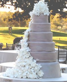 Cascading white flowers down tiered lavender wedding cake