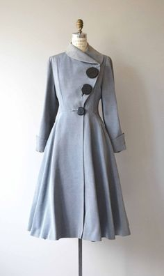 Maybe one of the most amazing coats ever? Vintage 1950s heavy weight rayon faille coat with asymmetrical shawl collar, asymmetrical graduated buttons starting with a collossal top button, fitted waist, large cuffs, hidden pockets, giant sweep and eggplant acetate lining. --- M E A S U R E M E N T S --- fits like: small/medium shoulder: 15 bust: up to 36 waist: 28.5 hip: free sleeve: 24, cuffed length: 46 brand/maker: n/a condition: excellent ★ layaway is available for this i...