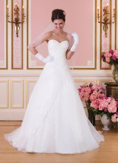 $873 Sweetheart style 6031 Organza and beaded lace asymmetrical draped A-line gown features a sweetheart neckline and apron skirt. Style is finished with a lace up back and chapel length train. White Size 20.
