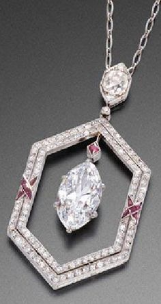 AN ART DECO RUBY AND DIAMOND PENDANT, CIRCA 1925. Of hexagonal shape, set with diamonds and accented by two crossed ribbons set with calibré rubies, centring a 3.66 carat marquise cut diamond, surmounted by a square cut ruby, with French assay marks, signed Fillon Orfèvre Joaillier, 26 rue Montaigne Paris, the cover monogrammed F.L.M.