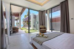 Hotels & Resort, Stunning Beach Villa Interior Design Featuring Bedroom Porcelain Tile Floor Wide Glass Window Curtain In White Scheme Single Sofa Green Grass Ocean View: Beach Villa Design in Open and Natural Concept besides Sea Panorama