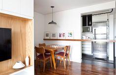 Sala de Jantar com bancada de apoio para os quadros e objetos. Destaque para os elementos em madeira: Piso de Madeira Mesa e Cadeira em Cumaru. O tecido na cor vermelho na cadeira compõe o jantar.