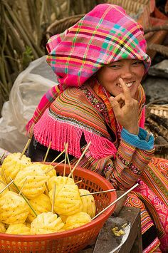 colorful Flower Hmong woman selling pineapples in the market in Cau Son, Vietnam