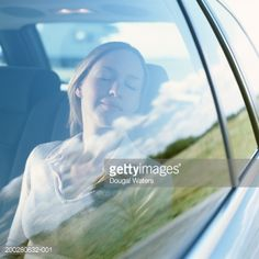 Stock Photo : Young woman in passenger seat of car, eyes closed, smiling