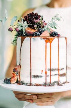 drizzle wedding cake topped with figs, flowers and berries
