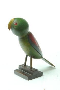 "Folk Art Parrot  Ohio 2nd Half 20th Century Wood.  Made by the ""Old Ohio Carver""  Simply carved with an oversize head and original green, red blue and yellow paint  11.5 inches h  Garths Auction Estimate $300 - 600"