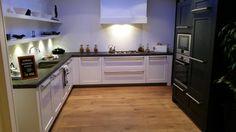 Massief houten keuken in wit hoogglans met antraciet hoge kasten.  http://www.grando.nl/vestigingen/grando-hoorn